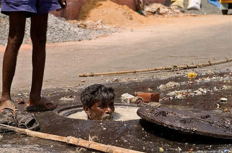 A worker in the sewer in Chennai, in front of Egmore station.